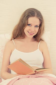 Beautiful Blonde Girl Reading A Book  In Bed Stock Photo