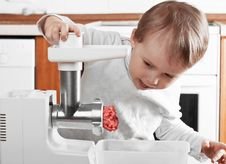 Little Boy Cutting Meat Royalty Free Stock Photos