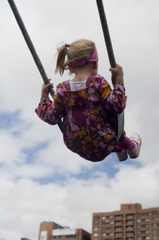 Free Little Girl Swinging In The City On Blue Sky Royalty Free Stock Photography - 23934747