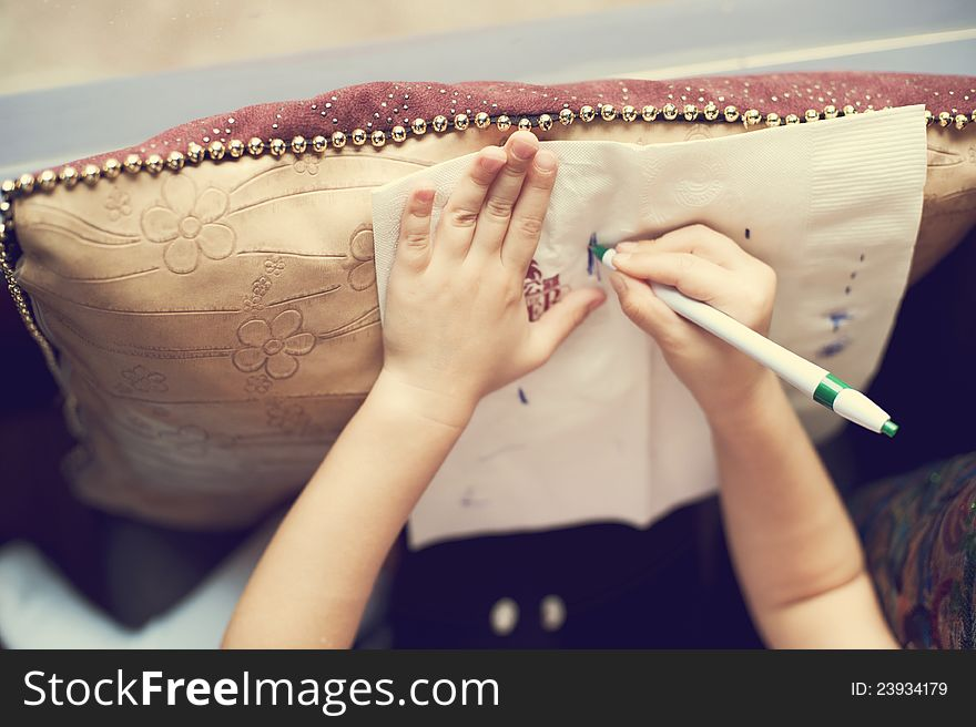 Girl s hands while drawing a picture on tissue