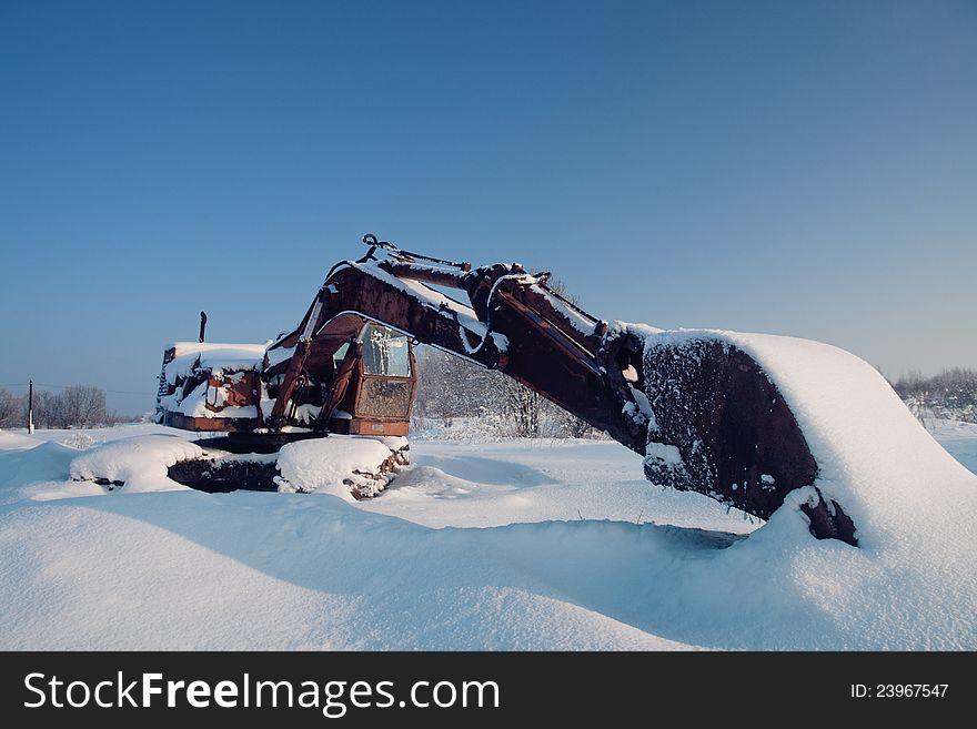 Unused excavator under  layer snow