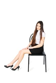Free Girl Wearing Skirt And Shirt Sits On Chair Royalty Free Stock Images - 24019479