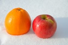 The Image Of Apple And Orange On Snow Stock Images