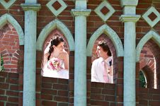 Free Happy Bride And Groom In Windows Of Brick Wall Royalty Free Stock Photos - 24085258