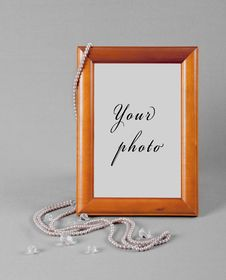 Beads Hang On A Frame For A Photo On Grey Fabric Royalty Free Stock Photos