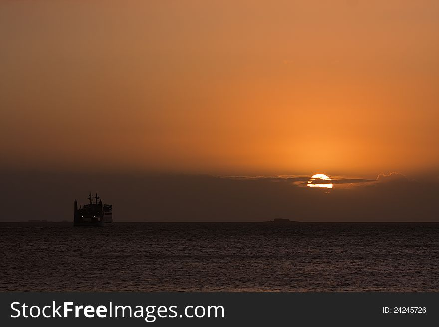 Sunrise over the sea with a ferry
