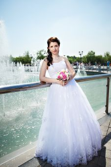Happy Bride About Fountain With Bouquet Stock Images