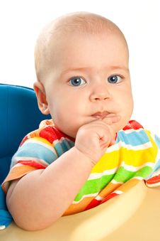 Little Baby Girl  Is Sitting At The Table Royalty Free Stock Image