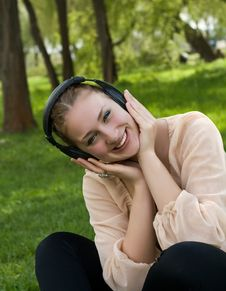 Happy Woman Sitting On Grass Listening To Music Royalty Free Stock Images