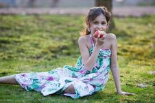 Young Girl Sits On A Meadow And Eats An Apple Royalty Free Stock Image