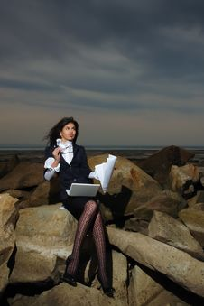 Business Lady Sitting On The Rocks By The Sea, Aga Stock Photo