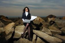 Business Lady Sitting On The Rocks By The Sea, Aga Royalty Free Stock Photos
