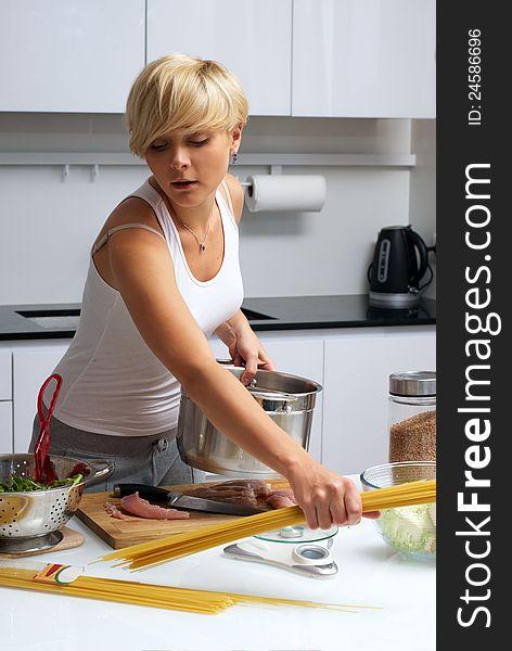 Pretty blond girl in the kitchen making pasta