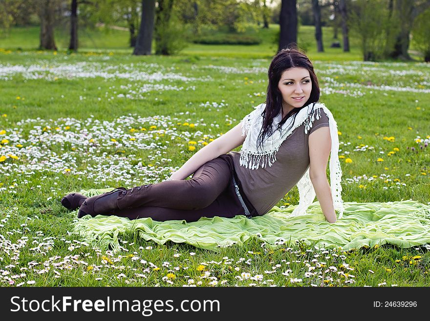 Beautiful girl sitting on the plaid in the park