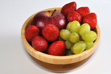 Apple With Grapes And Strawberries In Wooden Dish Stock Images
