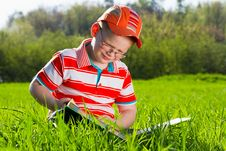 Free Young Boy Reads Book In Outdoor Park Stock Images - 24687584