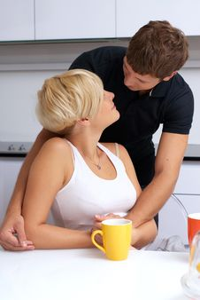 Happy Couple Posing In The Kitchen With Cups Stock Image