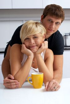 Happy Couple Posing In The Kitchen With Cups Royalty Free Stock Images