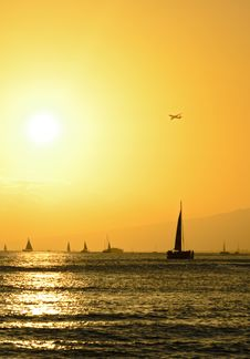 Sailboats And Airplane Over Hawaiian Sunset Royalty Free Stock Images