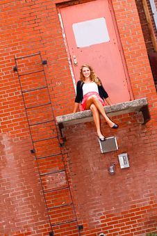 Pretty Teenage Girl Sitting On A Ledge Stock Photo