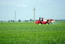 Free Red Tractor Waters A Cultivated Field Stock Photos - 24843183