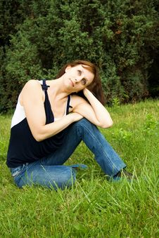 Woman Sitting On The Green Grass Stock Images