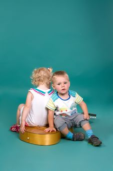 Girl And Boy Sitting On The Guitar Back To Back Stock Photography