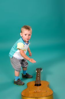 Boy Reaches For The Guitar Royalty Free Stock Image