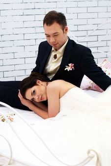 Free Bride And Groom Sitting On Bed In Bedroom Royalty Free Stock Images - 25255679