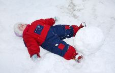 Little Tired Girl Lies On Snow Near Big Snowball Royalty Free Stock Image