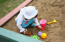 Llittle Girl Plays In Sandbox At Playground Stock Photo