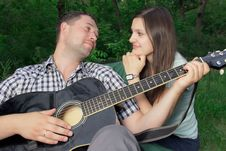 Free Romantic Young Couple Embracing Playing Guitar Royalty Free Stock Images - 25364629