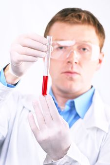 Free Man In White Coat Looking At A Red Sample Royalty Free Stock Photo - 25484455