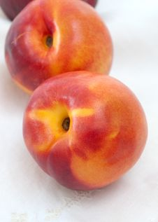 Two Nectarines And Embroidered Napkin Stock Images