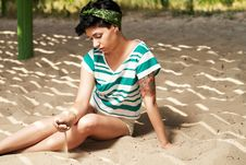 Girl With Tattoo On The Beach Pours Sand Royalty Free Stock Photo