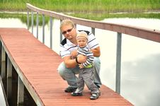 Free Father And Son  On  A Wooden Pier Near A River Royalty Free Stock Photos - 25767198
