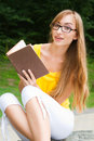 Free Young Woman Sitting On A Stone And Reading A Book Stock Image - 26040471