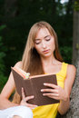 Free Young Woman Sitting Near A Tree,reading A Book Royalty Free Stock Photo - 26040525