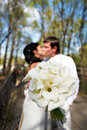 Free Bouquet Kala Against Romantic Kiss Bride And Groom Royalty Free Stock Image - 26053906