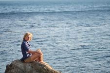Girl Is Sitting On A Rock Near The Sea Stock Images