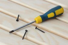 Free Screwdriver And Three Screws Over Wood Royalty Free Stock Images - 26209549