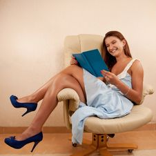 Free Girl Sitting In Chair Reading Book Stock Photography - 26563752