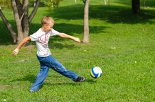 Free Young Boy Playing Football Outdoors Stock Image - 26687651