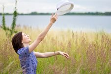 Young Woman Throwing Up The Hat Stock Photo