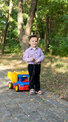 Free Boy Pulling A Toy Truck On A Paved Lane Stock Image - 26718631