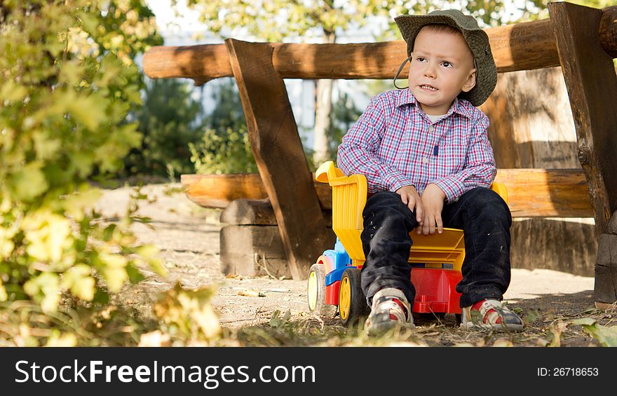 Young boy sitting in a toy dump truck