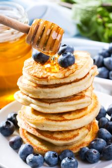 Pancakes With Pouring Honey Stock Photo