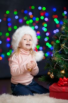 Baby Decorating Christmas Tree On Bright Backdrop Stock Image