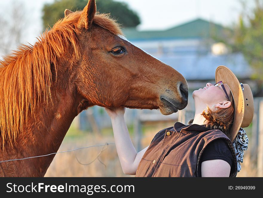 A horse leans in to give pretty young lady a kiss