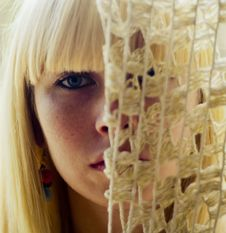 Blond Woman S Face Behind Net Stock Image